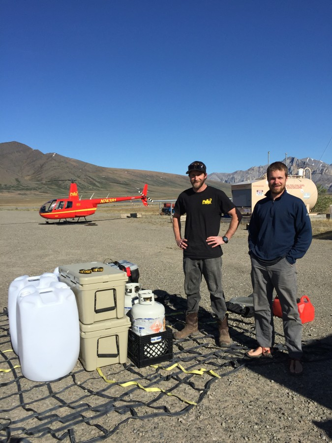 Photo Credit: Metta McGarvey. Nick and Ethan carefully arrange a load of large items such as our AV gas containers and Yeti coolers, along with most of our hazmat items, to be transported to camp with the helicopter sling.