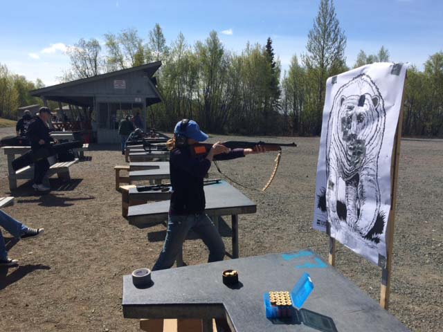 "Each year we are required to pass a firearms safety course, which we did in Anchorage under Rick Lanctot's expert guidance. In this photo, Metta takes aim at a bear target downrange, while the ""running bear,"" another target on wheels meant to mimic a charging bear, arrived at the firing station."