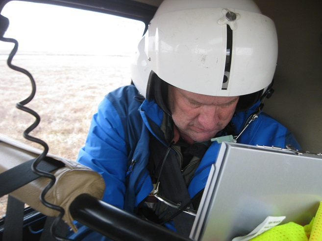 The helicopter is small, so we share close quarters.  Here is Brad preparing his data sheets just before getting deployed at a survey plot.