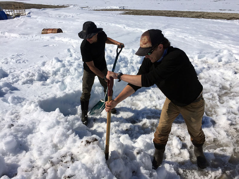 Shiloh Schulte and Scott Flemming clear a footprint for the food tent. The crew had to dig through snowdrifts to set up camp and gain access to the river for drinking water.
