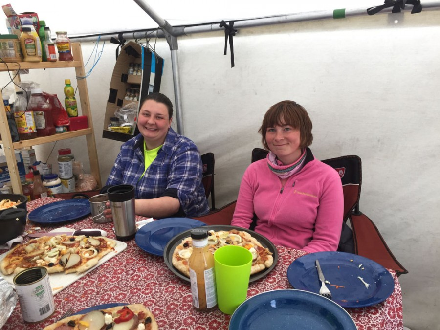 After a long day in the field, Shawna-Lee Masson and Lindy Spirak sit down to a dinner of gourmet pizza prepared by Malkolm Boothroyd.