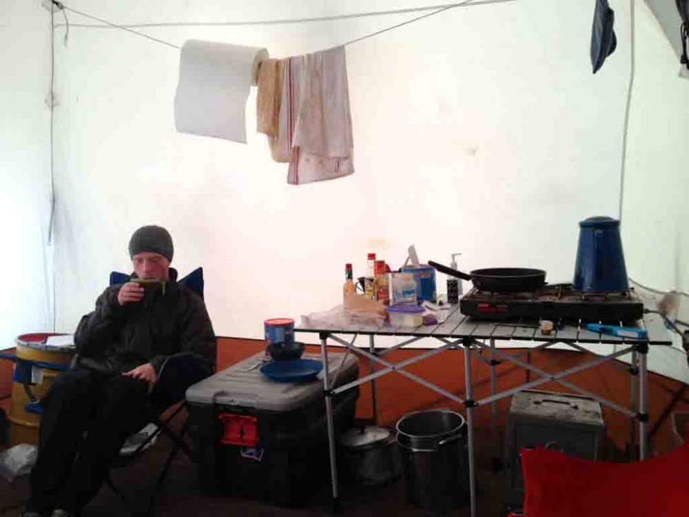 Brendan enjoys some hot chocolate after dinner in the cook tent. Food is kept in the barrel in the corner,  while pots and pans are kept below the table and in the box next to it.