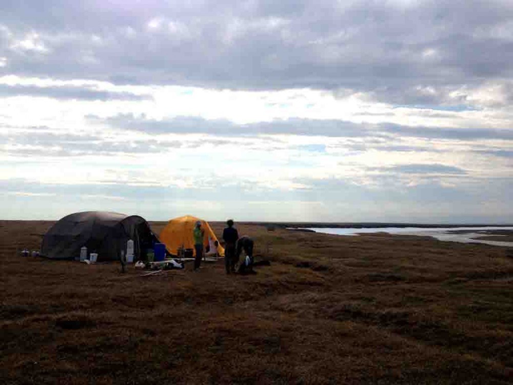 A few people in various stages of getting ready for the day. Cook tent on the left, office tent on the right, and bathroom in the back in the distance.